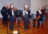 Rebecca Jennings and Wendy Oakes playing Bach's double violin concerto accompanied by a group of about eight other string players