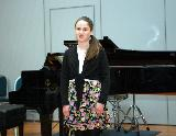 Evangeline introducing the piece by Chopin she is about to play on the Steinway